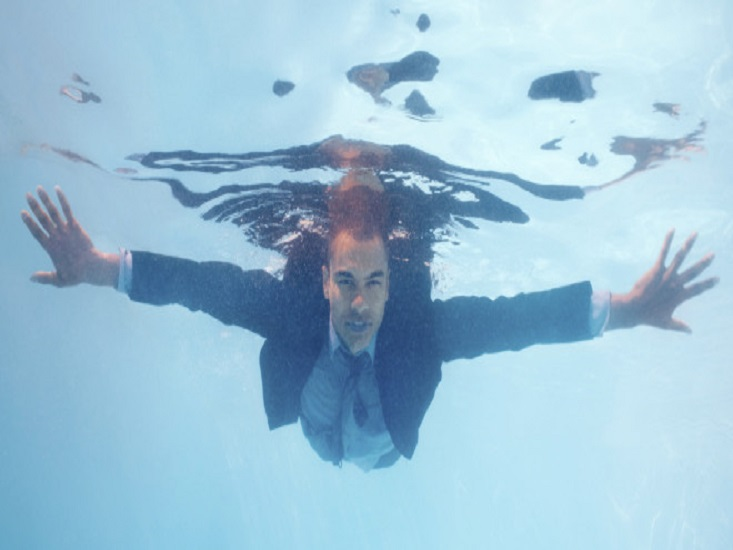 Portrait of a relaxed business executive diving under water in pool